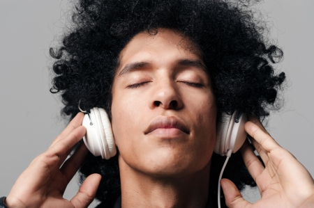portrait of a dj man listening to music on headphones with afro hairstyle isolated on grey background photo
