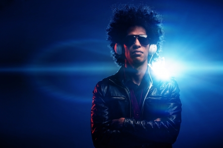 Cool nightclub party dj portrait with headphones lighting flare and sunglasses photo