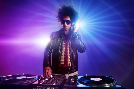 nightclub dj playing music on deck with vinyl record headphones light flare clubbing party scene Stock Photo - 16479795