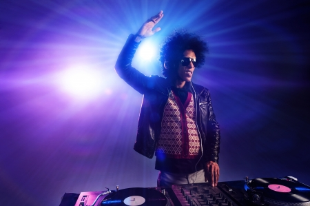 nightclub dj playing music on deck with vinyl record headphones light flare clubbing party scene Stock Photo - 16494753
