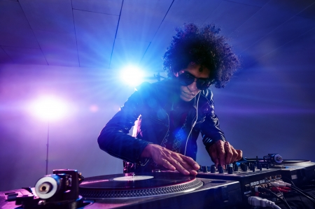 nightclub dj playing music on deck with vinyl record headphones light flare clubbing party scene photo