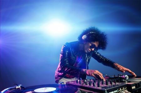 musica electronica: dj discoteca tocando música en la cubierta con disco de vinilo auriculares luz ambiente de fiesta llamarada discotecas