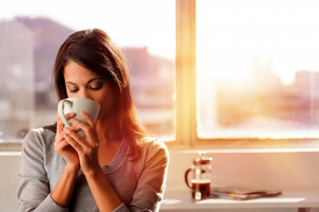 morning coffee: woman enjoys fresh coffee in the morning with sunrise at home lifestyle