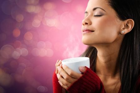 mujer tomando cafe: mujer disfrutando taza caliente de café humeante con las luces y el retrato hermoso bokey Foto de archivo