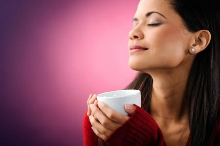 woman drinking tea: beautiful woman holding coffee mug with eyes closed enjoying the aroma