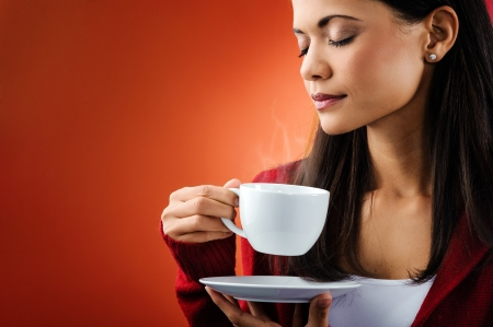 beautiful portrait of woman smelling fresh hot coffee with steam holding mug isolated on orange background Stock Photo - 16520996