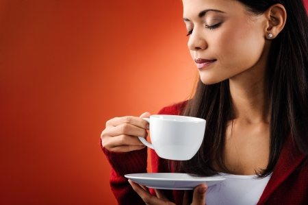 espresso cup: Woman smelling hot drink and holding mug isolated in studio