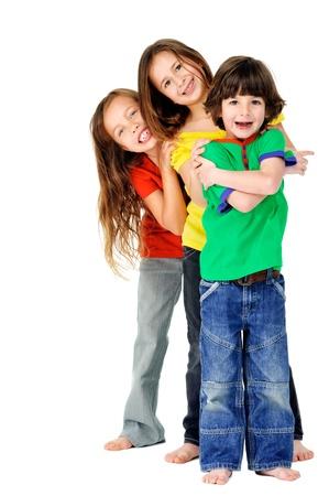 niño y niña: niños adorables lindos que se divierten junto con brillantes camisetas coloridas aisladas en el fondo blanco Foto de archivo