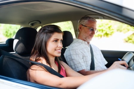 test drive: Learner driver student driving car with instuctor. happy and confident smiling girl Stock Photo