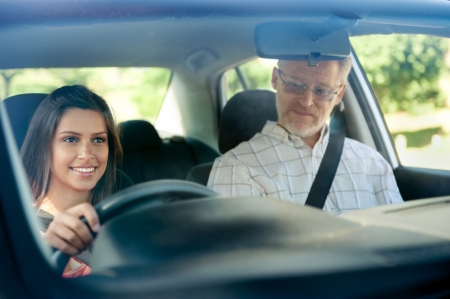 female driver: Learner driver student driving car with instuctor. happy and confident smiling girl Stock Photo