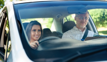 learner: Learner driver student driving car with instuctor. happy and confident smiling girl Stock Photo