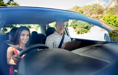 Learner driver student driving car with instuctor. happy and confident smiling girl photo