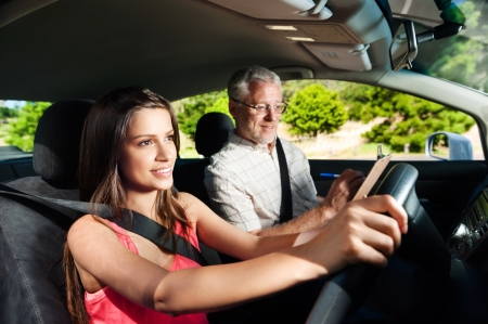shool: Learner driver student driving car with instuctor. happy and confident smiling girl Stock Photo