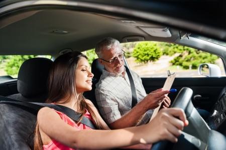 chofer: Estudiante aprendiz conductor que conduce el coche con instuctor. sonriente ni�a feliz y confiado Foto de archivo