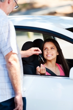 Student driver passes exam and instructor passes her keys photo