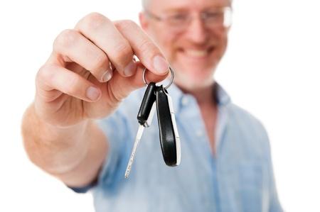 car keys: Mature car salesman success handing car keys to new owner