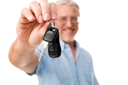 Mature car salesman success handing car keys to new owner photo