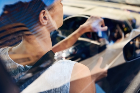 successful businesswoman driving car through modern urban city with reflections of buildings Stock Photo - 17635846