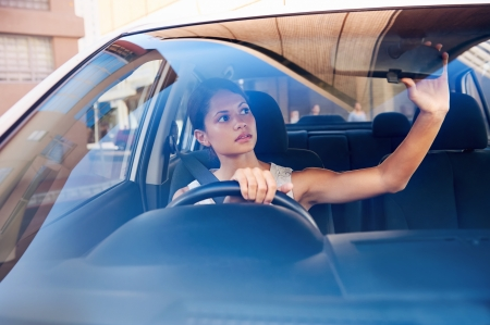 successful businesswoman driving car through modern urban city with reflections of buildings Stock Photo - 17635847