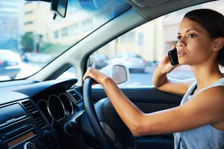 business car: businesswoman driving car and talking on cell phone concentrating on the road