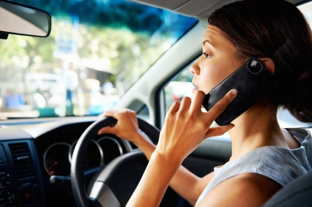 observant: businesswoman driving car and talking on cell phone concentrating on the road