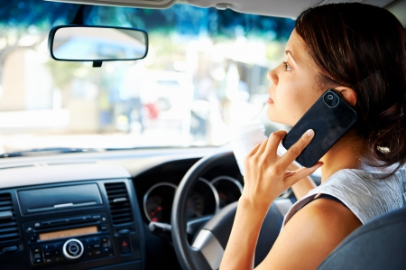 mobile phone adult: businesswoman driving car and talking on cell phone concentrating on the road