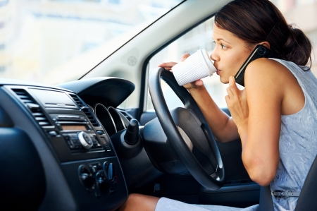 drinking driving: Businesswoman multitasking while driving, drinking coffee and talking on the phone Stock Photo