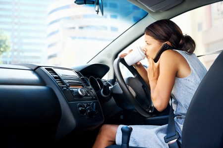 distracted: Businesswoman multitasking while driving, drinking coffee and talking on the phone Stock Photo