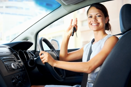 new automobiles: Happy woman new car owner smiling and showing keys in driver seat Stock Photo