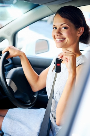 Happy woman new car owner smiling and showing keys in driver seat photo