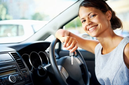 rental car: Happy woman new car owner smiling and showing keys in driver seat Stock Photo