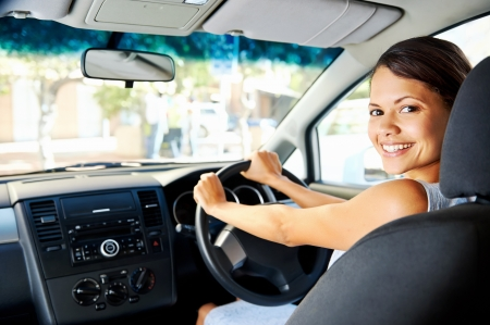 woman driving car: Happy woman new car owner smiling and showing keys in driver seat Stock Photo