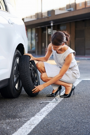 broken car: businesswoman in the city with flat tire frustrated Stock Photo
