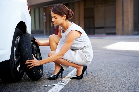 flat tyre: businesswoman in the city with flat tire frustrated Stock Photo