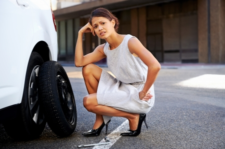 car tire: businesswoman in the city with flat tire frustrated Stock Photo