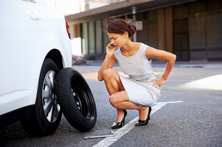 roadside assistance: Woman calling for assistance with flat tire on car in the city