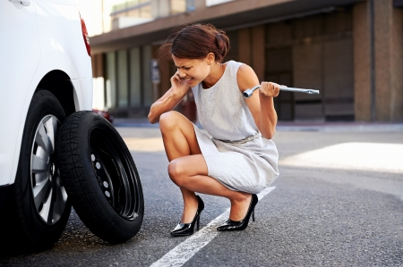 roadside: Woman calling for assistance with flat tire on car in the city