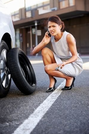 Woman calling for assistance with flat tire on car in the city Stock Photo - 17636352
