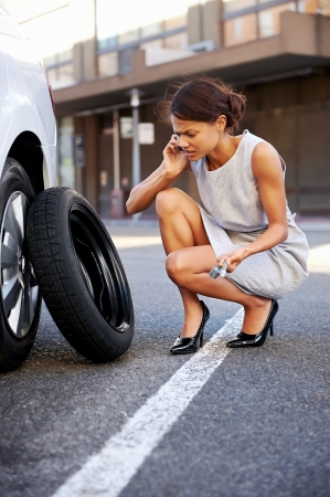 Woman calling for assistance with flat tire on car in the city photo