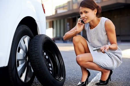 flat tyre: Woman calling for assistance with flat tire on car in the city