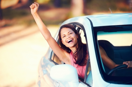 roadtrip: Happy woman waving from drivers seat in car while traveling