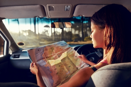 woman driving car: Woman on vacation looking at map for directions while driving in car Stock Photo