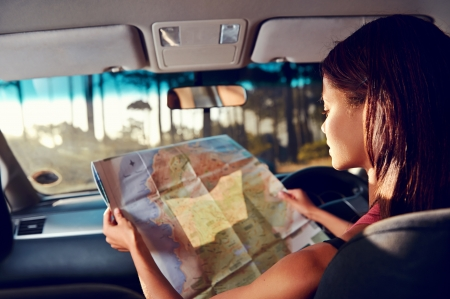 road: Woman on vacation looking at map for directions while driving in car Stock Photo