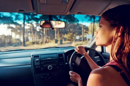 woman driving: Woman driving on vacation on country road happy and smiling