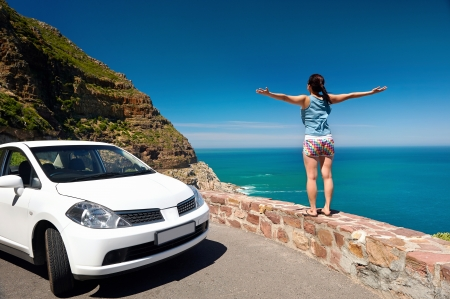 carefree tourist stands on chapmans peak drive with arms outstretched in freedom girl pose with rental car Stock Photo - 17636316