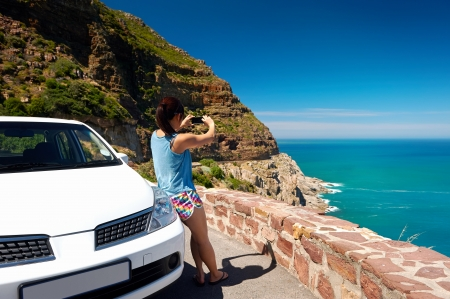 chapmans: Tourist woman taking a photograph of scenic ocean mountain road chapmans peak in cape town south africa with rental car Stock Photo