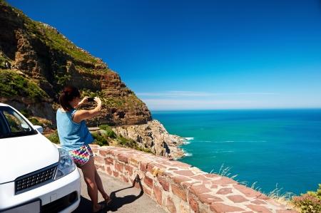 Tourist mujer que toma una fotografía de la pintoresca carretera de montaña océano Chapmans Peak en Ciudad del Cabo Sudáfrica con alquiler de coches