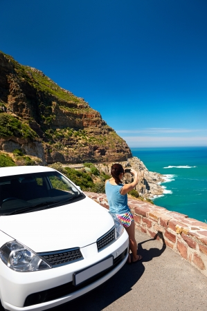 Tourist woman taking a photograph of scenic ocean mountain road chapmans peak in cape town south africa with rental car Stock Photo - 17636188