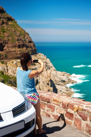 Tourist woman taking a photograph of scenic ocean mountain road chapmans peak in cape town south africa with rental car photo