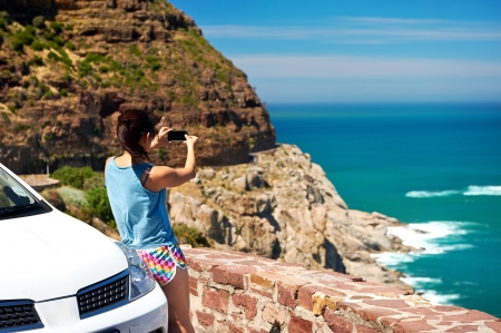 car rental: Tourist woman taking a photograph of scenic ocean mountain road chapmans peak in cape town south africa with rental car Stock Photo